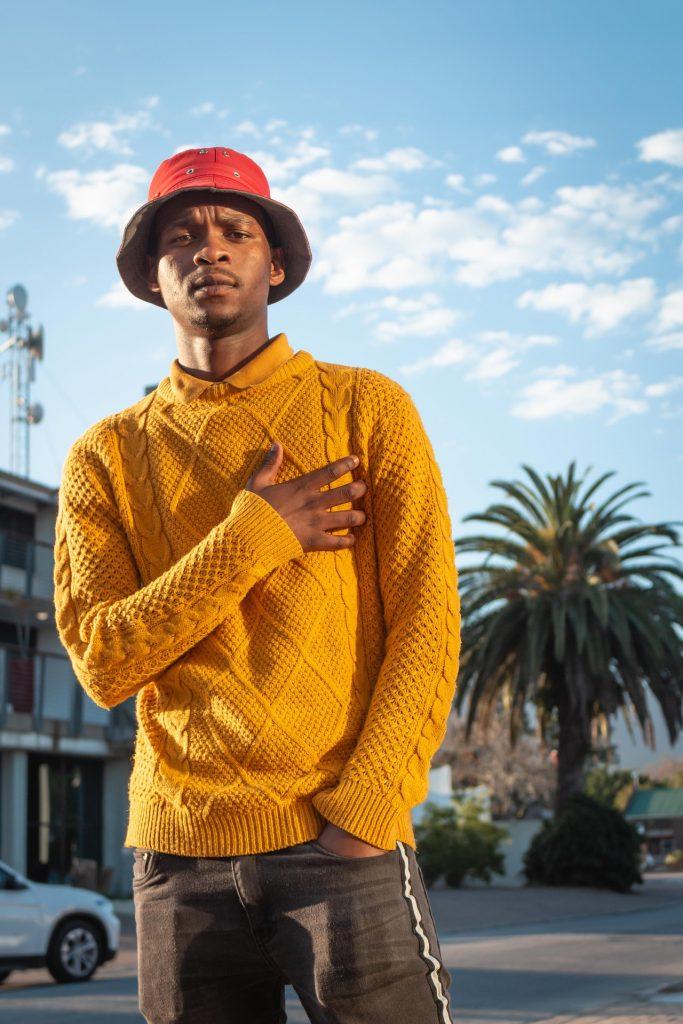 homme qui porte un pull jaune en laine