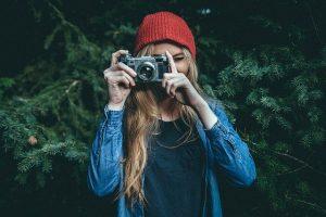 femme avec un appareil photo reflex de face prenant une photo